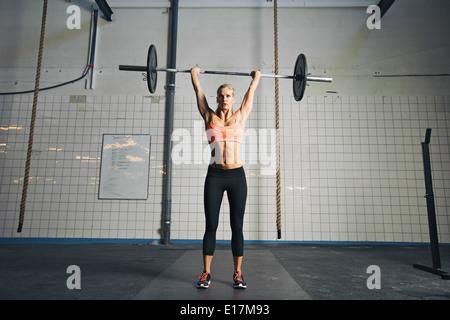 Longueur totale de l'image forte jeune femme avec des plaques de poids et haltères faire les frais généraux de l'exercice. Banque D'Images