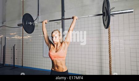 La jeune femme à l'haltérophilie gym crossfit. Mettre en place des poids lourds de levage modèle féminin au sport. Banque D'Images