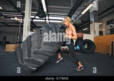 La jeune femme flipping tire au sport. Monter des pneus d'une athlète féminine à rabat. sport crossfit Banque D'Images