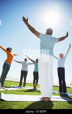 Seniors practicing yoga in sunny park Banque D'Images