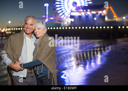 Senior couple hugging on beach at night Banque D'Images
