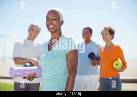 Portrait of smiling senior woman avec tapis de yoga in park Banque D'Images