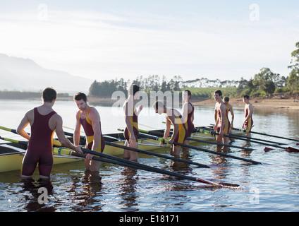 Placer l'équipe d'aviron sur le lac en bateau Banque D'Images