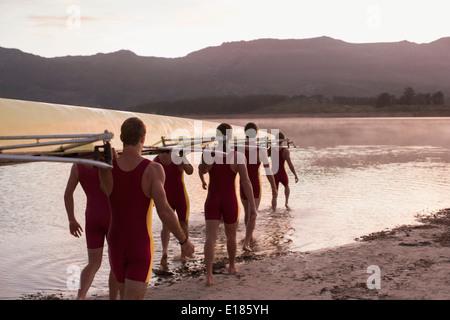L'exécution de l'équipe d'aviron de godille dans le lac à l'aube Banque D'Images