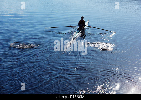 Man rowing scull on lake Banque D'Images