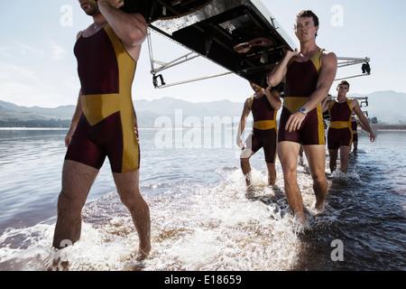 L'exécution de l'équipe d'aviron de godille sortant du lac Banque D'Images