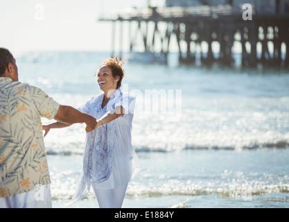 Enthousiaste couple dancing on sunny beach Banque D'Images