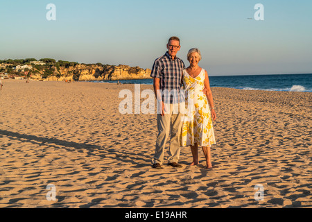 L'homme et de la femme debout sur une plage à la fin de soirée sunshine Banque D'Images