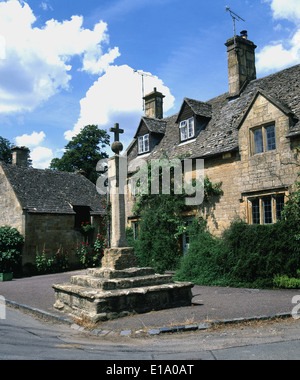 La croix de pierre médiévale dans le charmant village de Cotswold Stanton sur une journée d'été. Banque D'Images