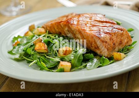 Saumon grillé avec pommes de terre rôties et salade de roquette. Banque D'Images