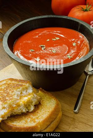 Un petit bol de soupe aux tomates faites maison et un sandwich au fromage. Banque D'Images
