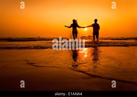 Silhouettes de couple running à la mer sur la plage au coucher du soleil Banque D'Images