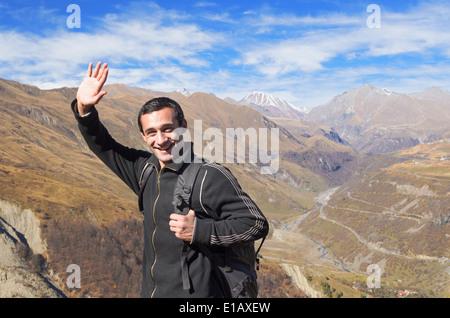 Happy tourist traveler avec un sac à dos noir dans les montagnes, souriant se félicite de part Banque D'Images