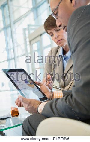 Les gens d'affaires de l'examen des données financières sur la tablette numérique Banque D'Images