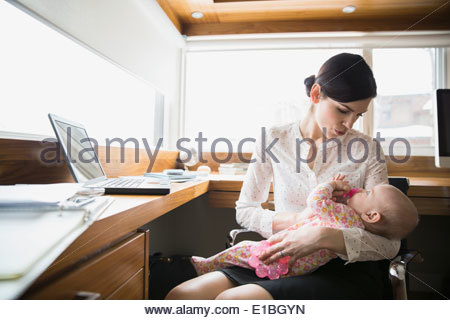 Mother holding baby in home office Banque D'Images