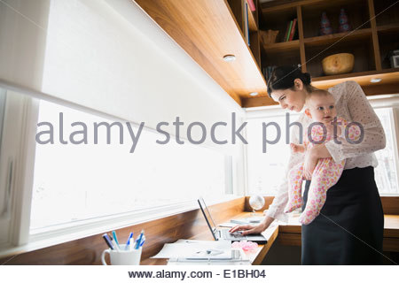 Mother holding baby and using laptop in office Banque D'Images