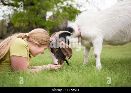 A girl lying on grass en tête à tête avec une chèvre. Banque D'Images