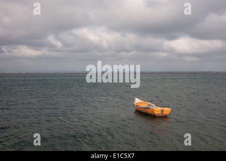 Un petit bateau en bois amarré à ouvrir l'eau, au large de la côte portugaise. Banque D'Images