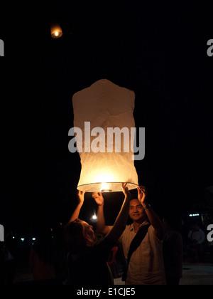 Les participants se préparent à lancer des lanternes flottantes dans l'air pendant l'Yi Peng festival à Luang Prabang, Banque D'Images