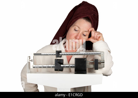 Young woman in bathrobe debout sur une balance de salle à la malheureuse Banque D'Images