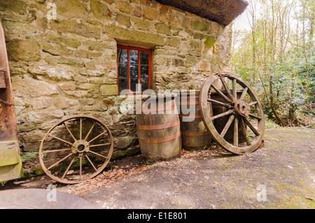 Barils et roues à l'extérieur d'un vieux irlandais farm cottage Banque D'Images
