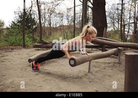 Tough young woman doing pushups sur un journal à parc. Jeune femme fit l'exercice dans les bois. Banque D'Images