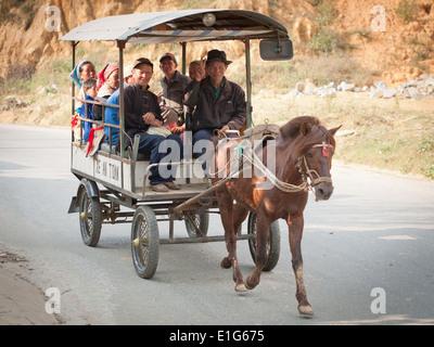 Une famille Flower Hmong balade en chariot juste à l'extérieur de Bac Ha, province de Lao Cai, Vietnam. Banque D'Images