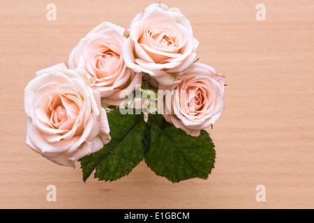 Roses roses dans un vase sur un bureau en bois Banque D'Images
