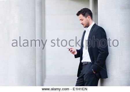 Young businessman leaning against wall la lecture de textes sur le smartphone. Banque D'Images