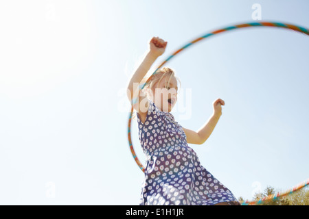 Low angle view of girl Playing with plastic hoop Banque D'Images