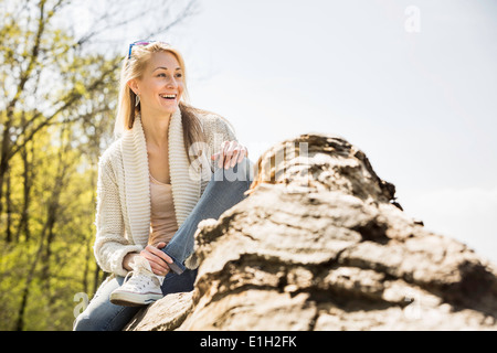 Smiling young woman sitting in forest Banque D'Images