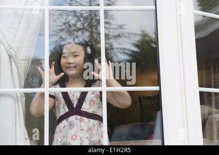 Jeune fille à la fenêtre de salon Banque D'Images