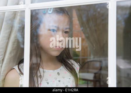 Malheureux jeune fille à la fenêtre de salon Banque D'Images