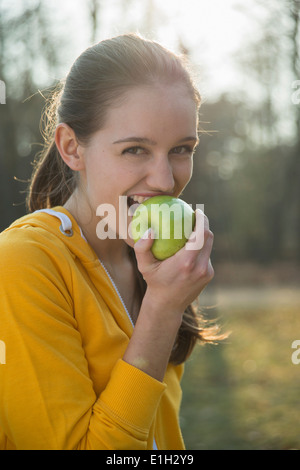 Portrait of young female runner eating an apple