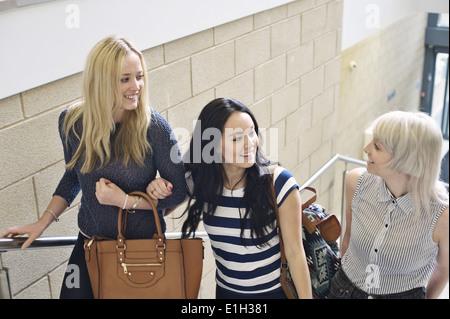 Trois jeunes femmes à parler d'escalier Banque D'Images