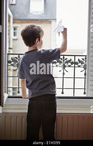 Lancement de l'avion en papier garçon window Banque D'Images