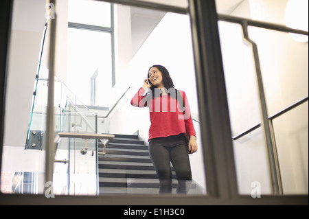 Young woman using cell phone on staircase Banque D'Images