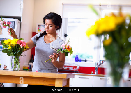 Young woman arranging flowers in kitchen Banque D'Images