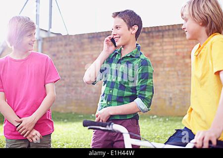 Boy using cell phone avec deux amis Banque D'Images