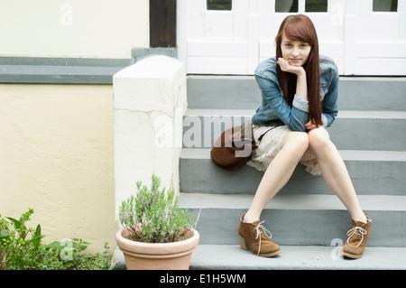 Portrait de jeune femme assise sur les marches de la chambre Banque D'Images