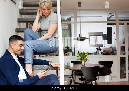 Jeune homme et femme assis sur les escaliers, looking at smartphone Banque D'Images