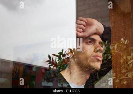 Jeune homme avec la main sur la tête, à la recherche d'une fenêtre