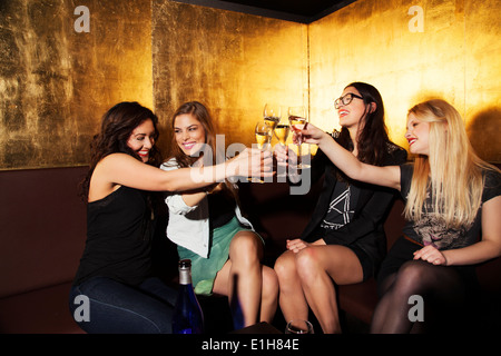 Quatre femmes friends toasting with wine in nightclub Banque D'Images