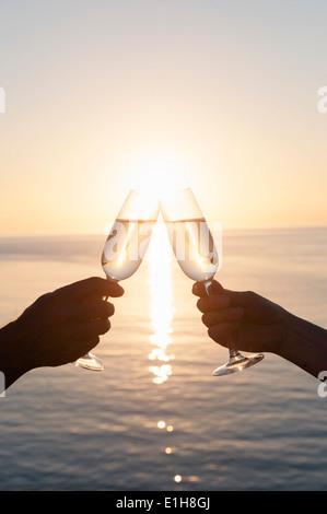 Couple toasting contre coucher du soleil Banque D'Images