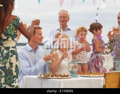 Couple à réception de mariage faire un toast avec des amis Banque D'Images