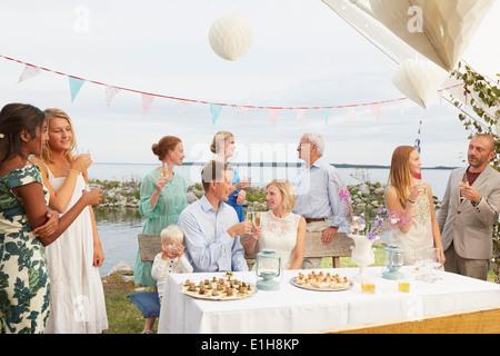 Couple faire un toast avec des amis à réception de mariage Banque D'Images
