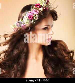 Portrait de jeune femme Auburn avec des poils longs et des fleurs sauvages Banque D'Images