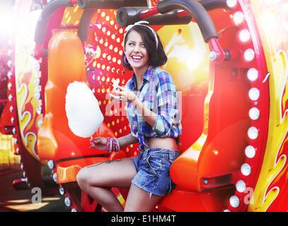 Style de vie. Young Happy Woman Eating Cotton Candy sucré en fête foraine Banque D'Images