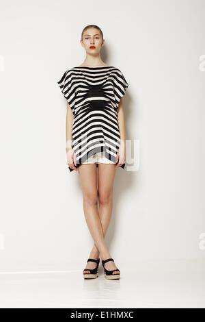 L'attitude. Femme chic moderne élégant gris en vêtements. Jambes croisées Banque D'Images