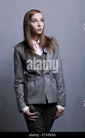 Modèle à la mode Trendy girl posing en posant costume gris. Studio shot Banque D'Images